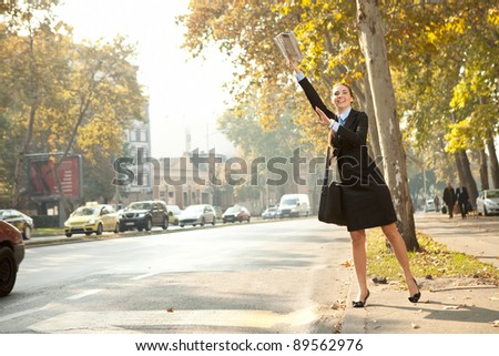 Businesswoman trying to hail a cab in the city - stock photo
