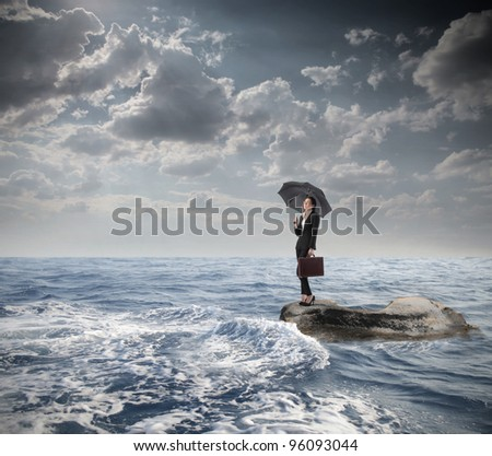 Businesswoman under an umbrella standing on a rock in the middle of a slight sea