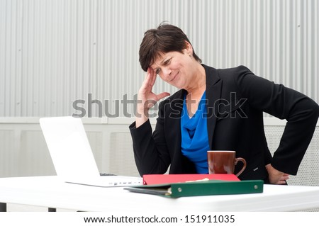 businesswoman under stress, fatigue, and headache at office - stock photo