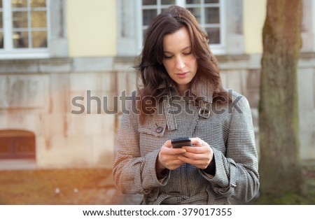 Businesswoman use her mobile phone outdoor in a historic village