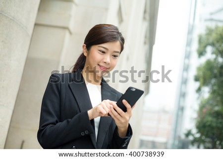 Businesswoman use of cellphone at outdoor in Hong Kong