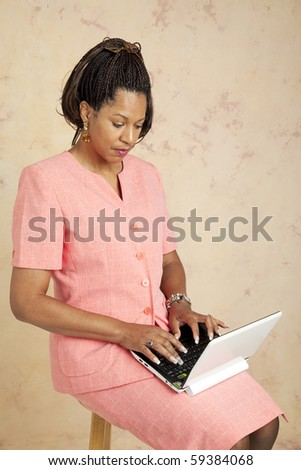 Businesswoman uses a tiny netbook computer to access the internet.