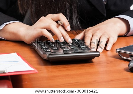 Businesswoman using a calculator on his desk - stock photo