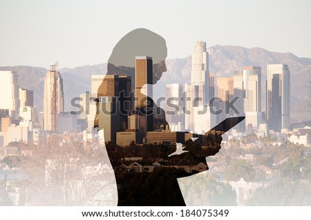 Businesswoman using a computer tablet composited with a cityscape of Los Angeles  - stock photo