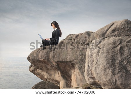Businesswoman using a laptop on a rock - stock photo