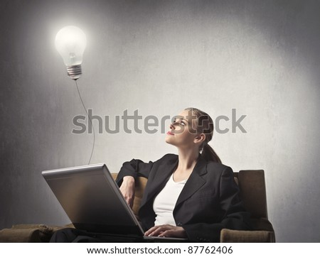 Businesswoman using a laptop with light bulb attached to it - stock photo