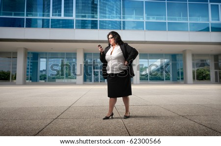 Businesswoman using a mobile in front of an office building - stock photo