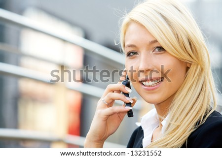 Businesswoman using a mobile phone and smiling