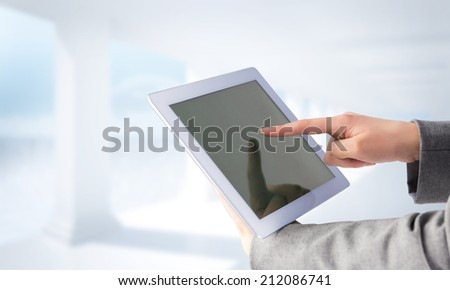 Businesswoman using a tablet pc against bright white room with columns - stock photo