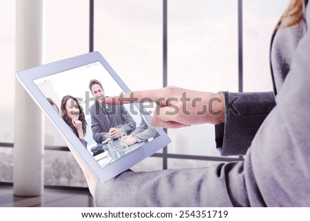 Businesswoman using a tablet pc against portrait of a positive team sitting at a table - stock photo