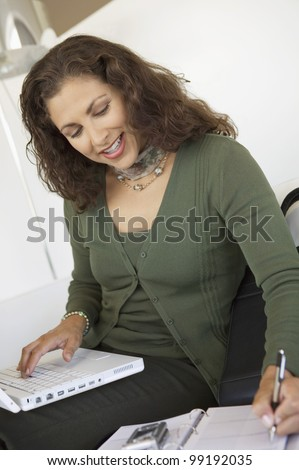 Businesswoman Using Cell Phone and Organizer - stock photo