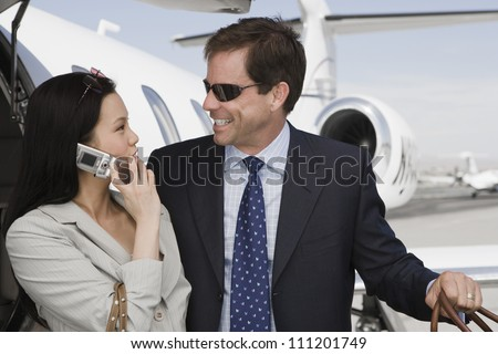 Businesswoman using cell phone while looking at businessman with airplane in background - stock photo