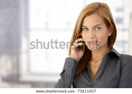 Businesswoman using cellphone, looking at camera, smiling.? - stock photo