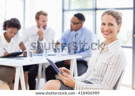 Businesswoman using digital tablet in office while colleagues discussing in background