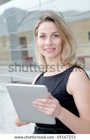 Businesswoman using electronic tab outdoors