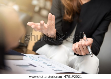 Businesswoman using hand gesture while sitting and talking in the meeting