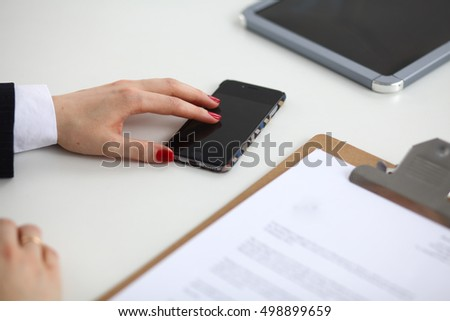 Businesswoman using her phone in office sitting on desk .