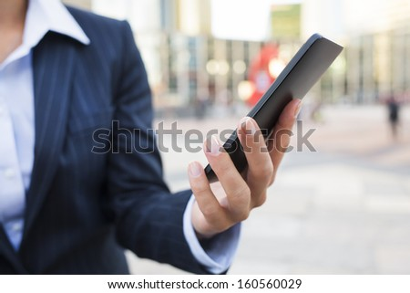 Businesswoman using her smart phone in front of Building  - stock photo