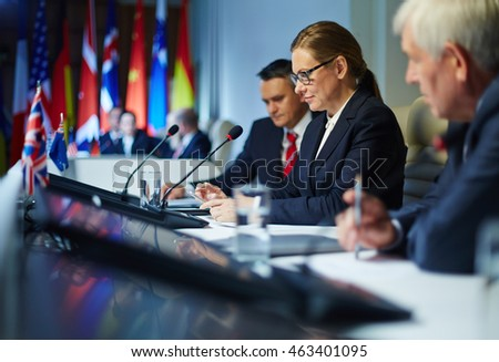 Businesswoman using her smartphone during the conference