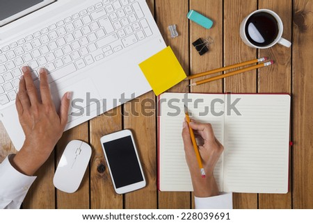 Businesswoman using laptop and  on her office table - stock photo