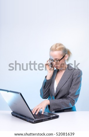 businesswoman using laptop computer and mobile phone - stock photo