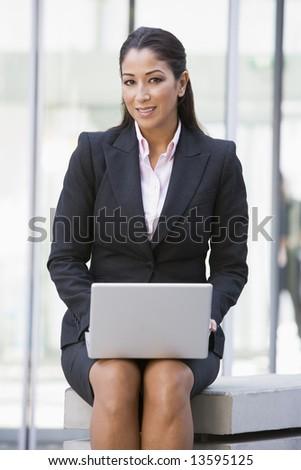 Businesswoman using laptop computer outside - stock photo