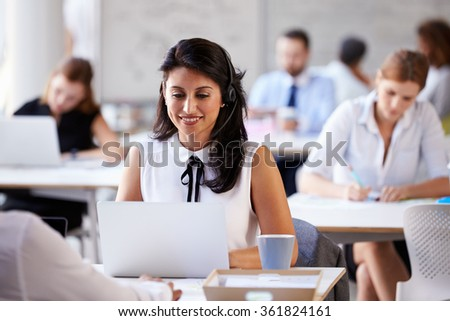 Businesswoman Using Laptop In Customer Service Department - stock photo