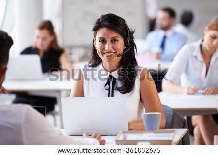 Businesswoman Using Laptop In Customer Service Department - stock photo