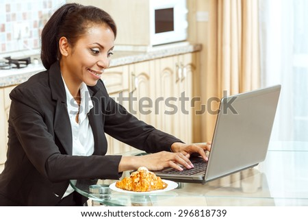Businesswoman using laptop in the kitchen - stock photo