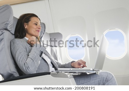 Businesswoman using laptop on airplane - stock photo