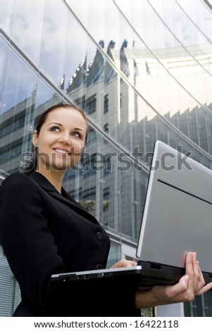 Businesswoman using laptop outside office - stock photo