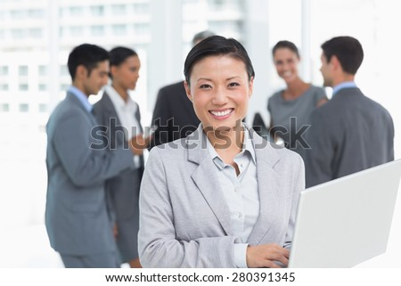 Businesswoman using laptop with colleagues behind in office