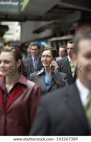 Businesswoman using mobile phone amidst coworkers while looking away - stock photo