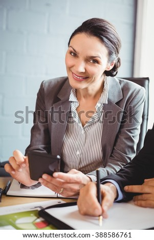 Businesswoman using mobile phone in conference room - stock photo