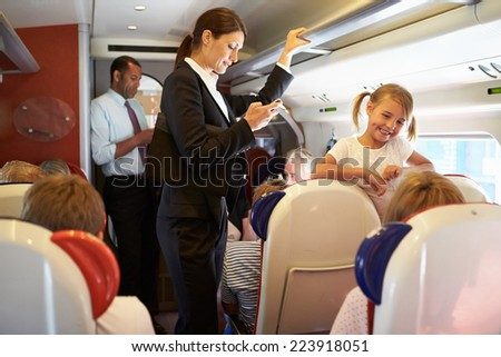 Businesswoman Using Mobile Phone On Busy Commuter Train - stock photo