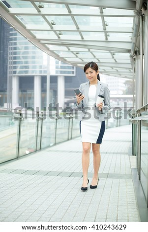 Businesswoman using mobile phone to send a message - stock photo
