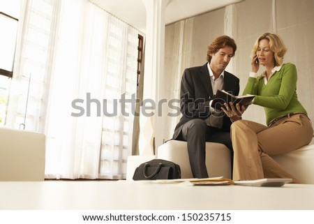 Businesswoman using mobile phone while reading notes with coworker in office lobby - stock photo