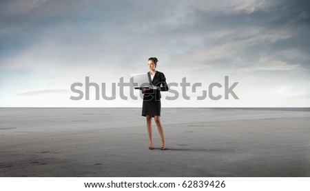 Businesswoman using on a laptop in a desert - stock photo
