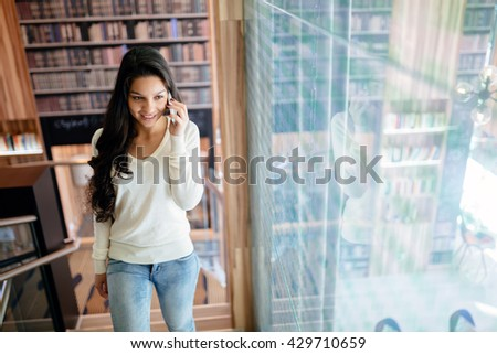Businesswoman using phone indoors and smiling