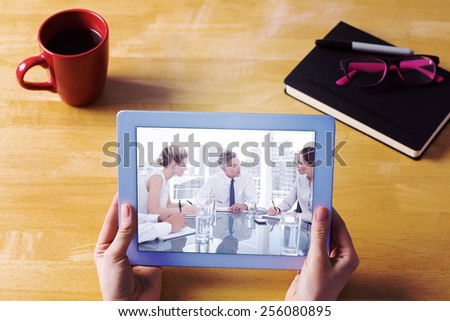 Businesswoman using tablet at desk against serious businessman during a meeting talking to his employees - stock photo