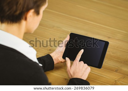 Businesswoman using tablet at desk shot in studio - stock photo
