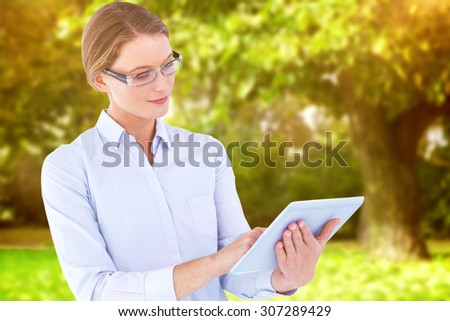 Businesswoman using tablet pc against trees and meadow in the park - stock photo