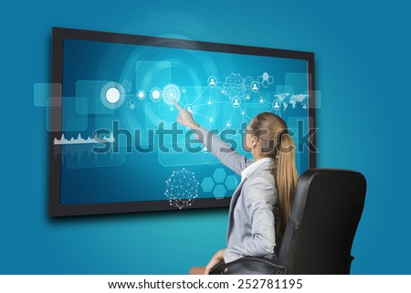 Businesswoman using touch screen interface with network of person icons, graph and other elements, on blue background - stock photo
