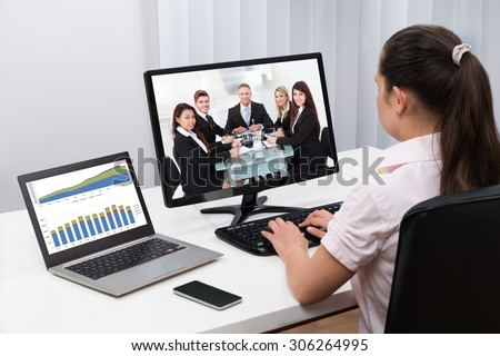 Businesswoman Videoconferencing With Colleagues On Computers At Desk