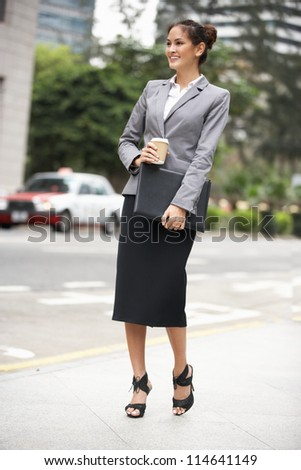 Businesswoman Walking Along Street Holding Takeaway Coffee - stock photo