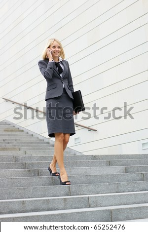 Businesswoman walking down stairs - stock photo