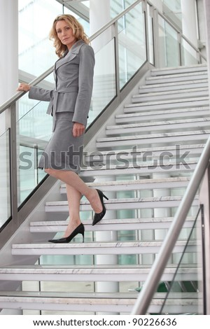 Businesswoman walking down steps - stock photo