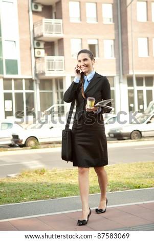 businesswoman walking on street of urban city - stock photo