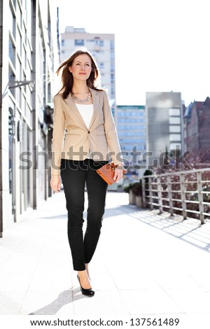 Businesswoman walking outdoors - stock photo