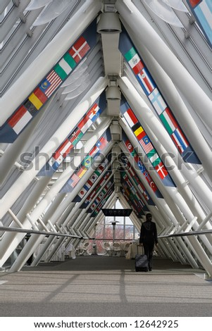 Businesswoman walking through a walkway / skybridge pulling her luggage behind her. The walkway is lined with flags. Vertically framed shot with the woman walking away from the camera.